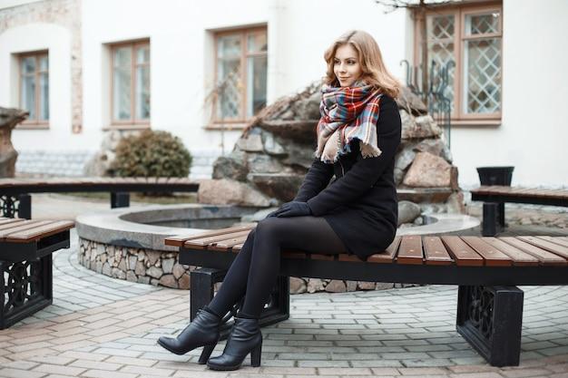 Mujer joven elegante relajándose en un banco