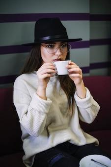 Mujer joven elegante en sombrero y lentes con taza de bebida