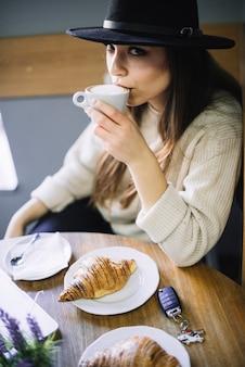Mujer joven elegante en sombrero con la taza de bebida en la tabla en café