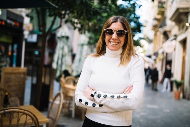 La mujer joven elegante sonriente con las gafas de sol acerca al café de la calle en ciudad