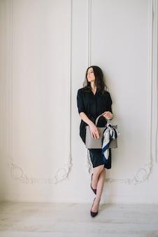 Mujer joven elegante en vestido con el bolso cerca de la pared en la habitación