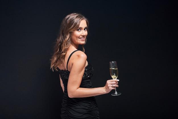 Mujer joven en elegante vestido con copa de champán contra negro