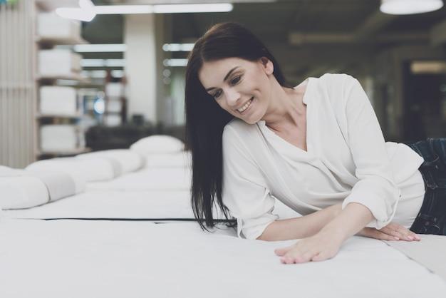 La mujer joven elige un colchón en una tienda.