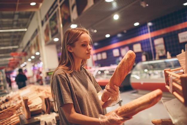 Mujer joven elige pan en la tienda