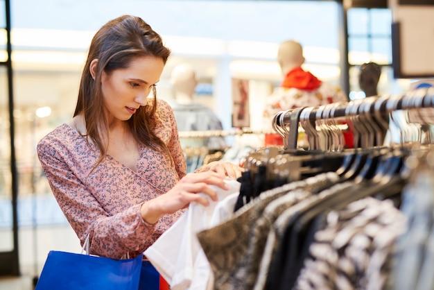 Mujer joven eligiendo blusa en la tienda de ropa
