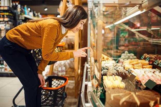 Mujer joven eligiendo pasteles en la tienda de comestibles, departamento de dulces.