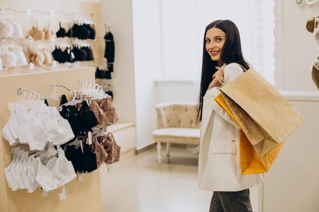 Mujer joven eligiendo ropa interior en el centro comercial