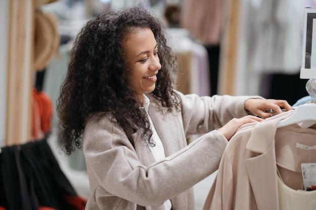 Mujer joven eligiendo ropa en la tienda