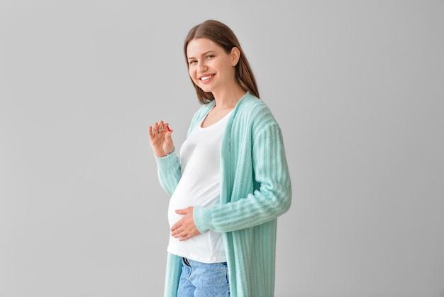 Mujer joven embarazada con píldora sobre superficie gris