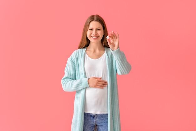 Mujer joven embarazada con píldora en la superficie de color