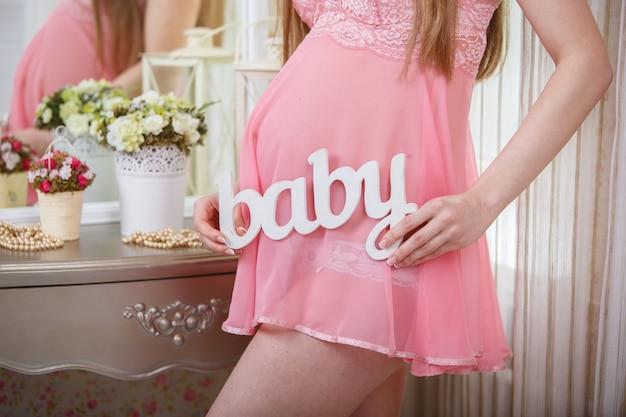Mujer joven embarazada en ropa interior hermosa en dormitorio de cerca. retrato de una atractiva embarazada con un vestido rosa.