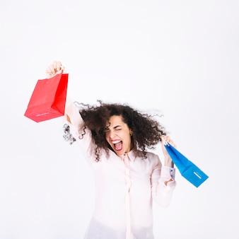 Mujer joven emocionada con bolsas de papel
