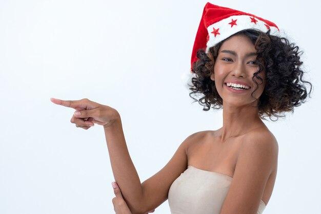 Mujer joven emocionada feliz en el sombrero de papá noel y el dedo del indicador