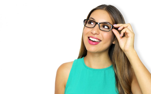 Mujer joven emocionada con gafas mirando hacia el lado