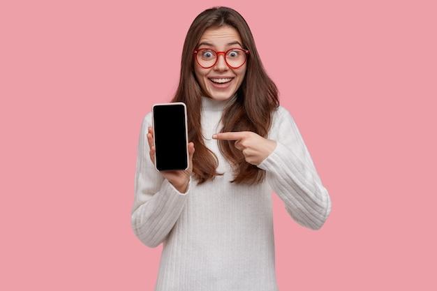 Mujer joven emocionada sin palabras apunta a la pantalla simulada del teléfono inteligente, intenta mostrar algo increíble, usa un jersey blanco