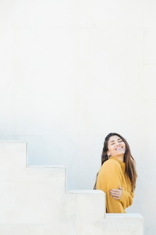 Mujer joven emocionada de pie contra la pared blanca