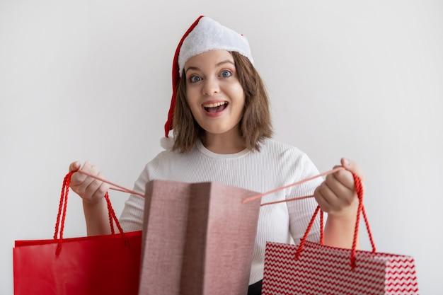 Mujer joven emocionada que abre el bolso de compras y que mira la cámara