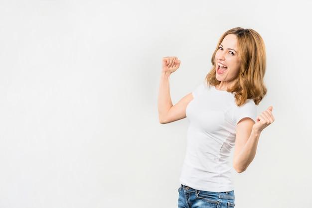 Mujer joven emocionada que aprieta su puño contra el contexto blanco