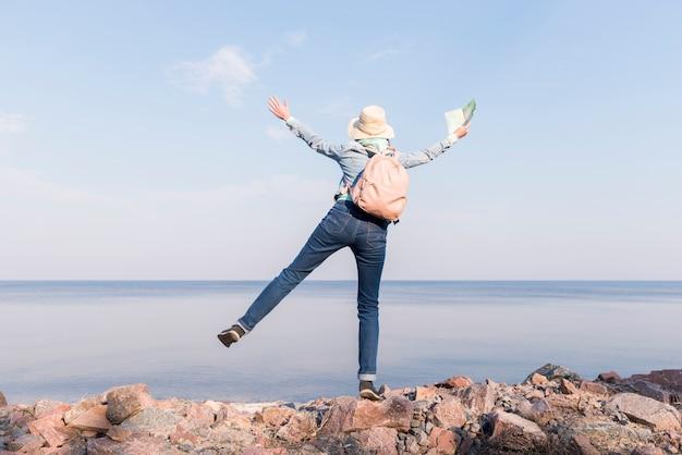 Mujer joven emocionada que se coloca encima de la roca que sostiene el mapa en la mano que pasa por alto el mar contra el cielo azul