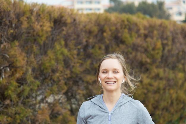 Mujer joven emocionada que corre en parque del otoño