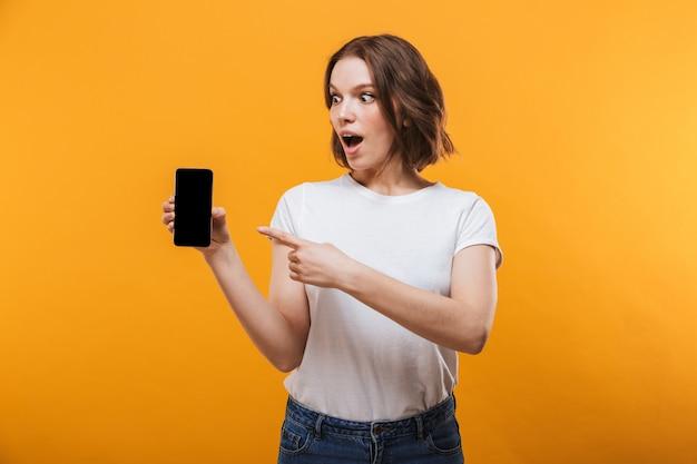 Mujer joven emocionada que muestra la pantalla de por teléfono móvil