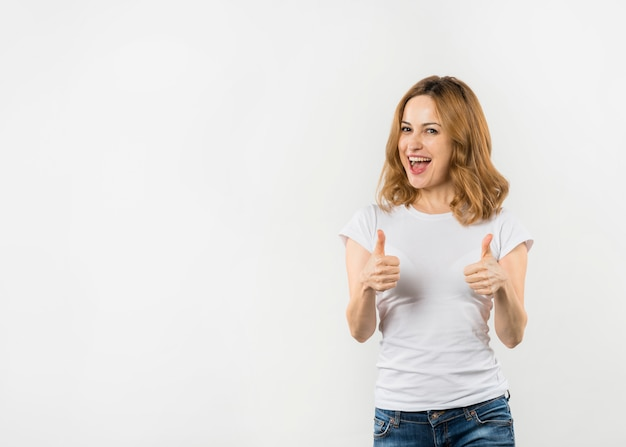 Mujer joven emocionada que muestra el pulgar encima de la muestra aislada en el contexto blanco