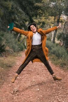 Mujer joven emocionada que sostiene el libro en la mano que salta en el camino