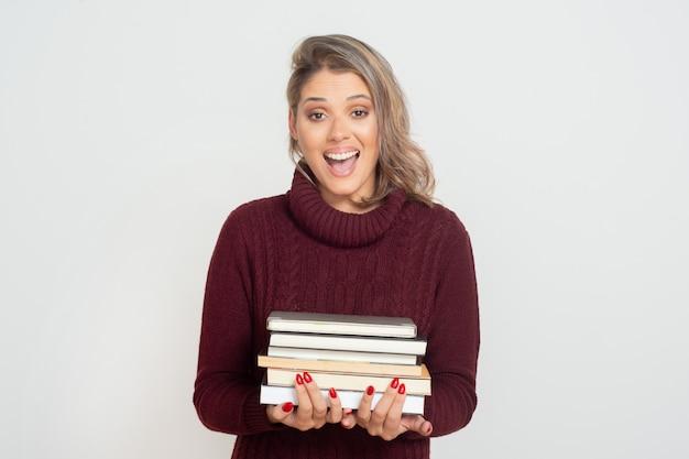 Mujer joven emocionada que sostiene los libros