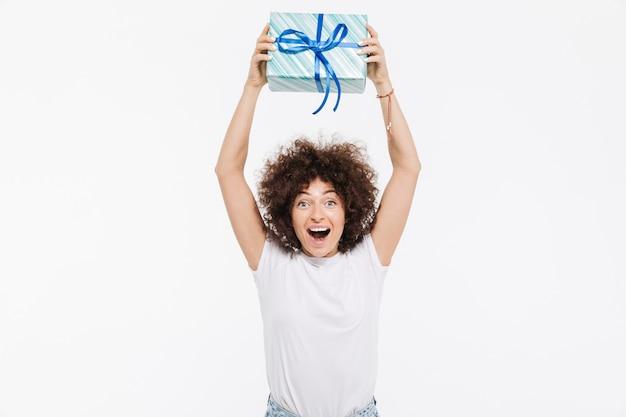 Mujer joven emocionada que sostiene el presente cuadro sobre su cabeza