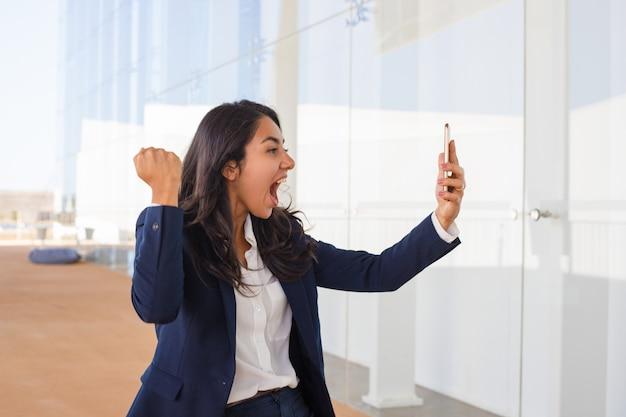 Mujer joven emocionada que sostiene smartphone