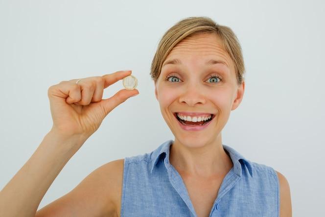 Mujer joven emocionada que sostiene una moneda euro