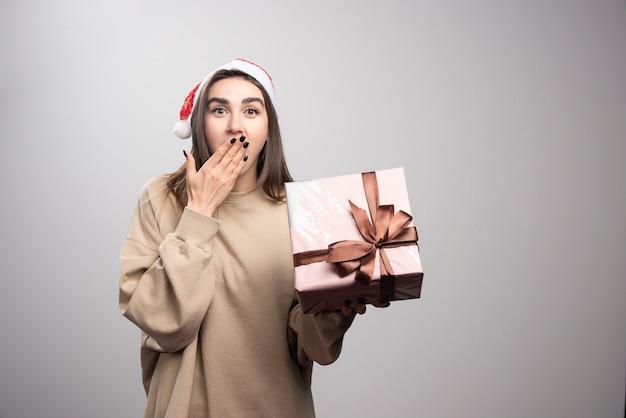 Mujer joven emocionada por un regalo de navidad.
