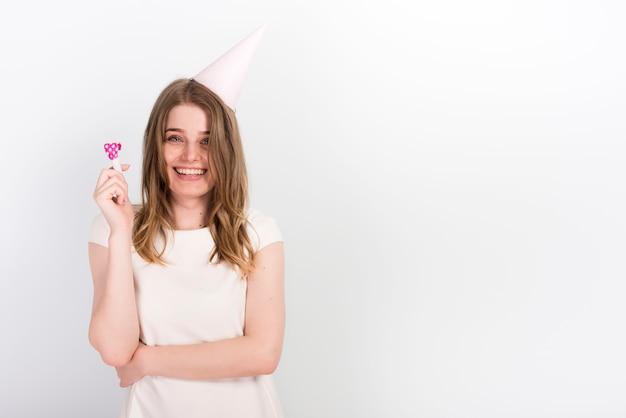 Mujer joven emocionada en el sombrero del partido que se divierte