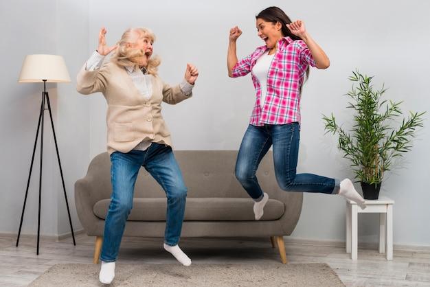 Mujer joven emocionada y su madre que saltan en aire en casa