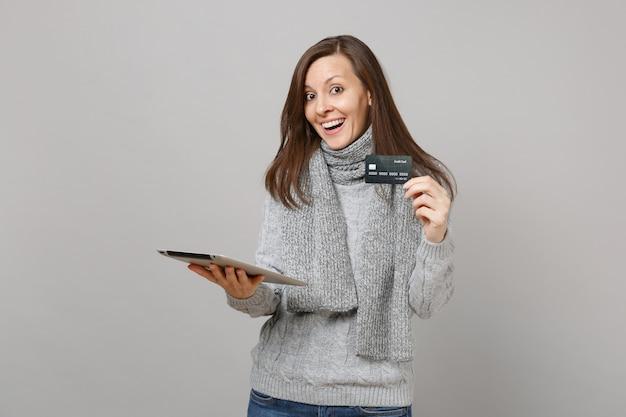 Mujer joven emocionada en suéter gris, bufanda con tablet pc y sosteniendo una tarjeta bancaria de crédito aislada sobre fondo de pared gris. estilo de vida saludable, consultoría de tratamiento en línea, concepto de estación fría.
