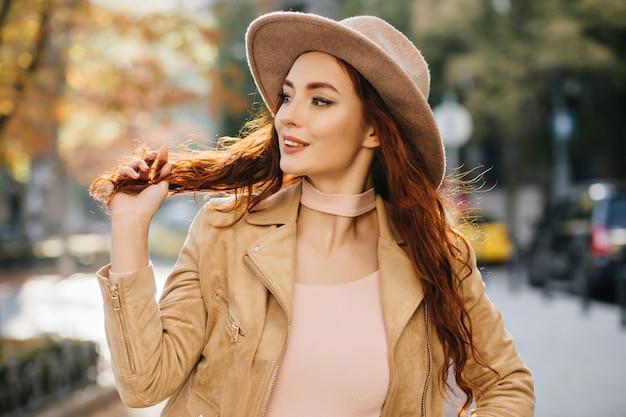 Mujer joven emocionada en traje elegante mirando a otro lado y jugando con el pelo de jengibre