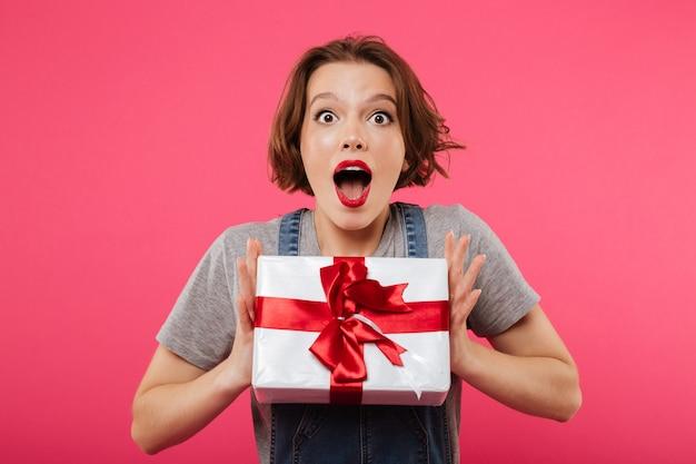 Mujer joven emocional con caja de regalo.