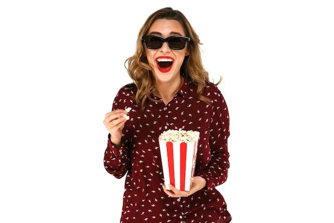 Mujer joven emocional con palomitas viendo la película de éxito en vidrios estéreo