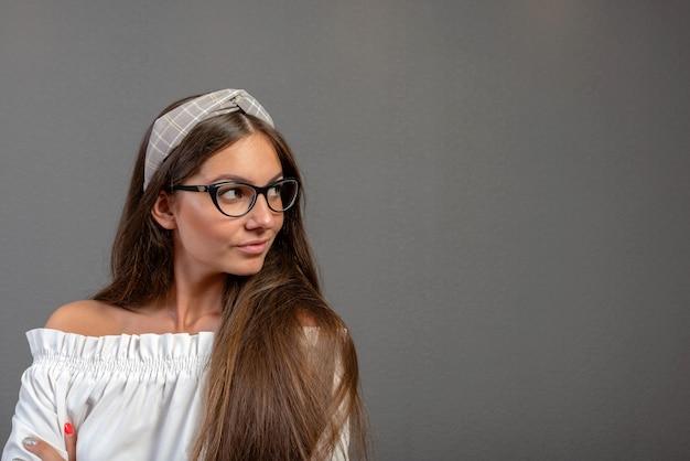 Mujer joven emocional con eyeglases sobre fondo oscuro con espacio de copia