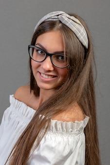 Mujer joven emocional con eyeglases sobre fondo oscuro