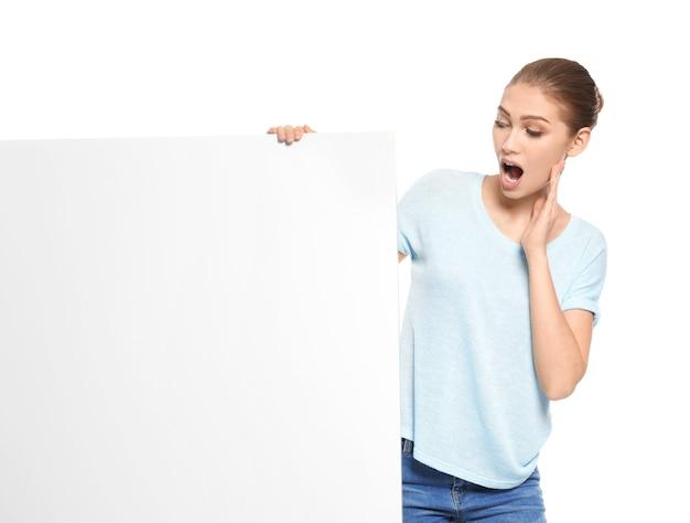 Mujer joven emocional con tablero publicitario en blanco sobre blanco