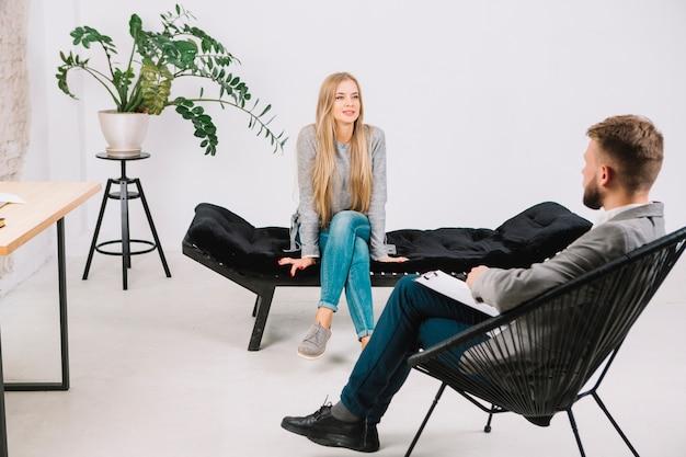 Mujer joven emocionalmente hablando y discutiendo con su psicoterapeuta sus problemas.