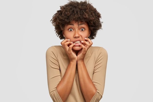 Mujer joven emotiva estresante mantiene las manos cerca de la boca