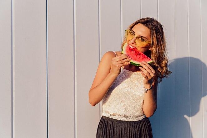 Mujer joven en gafas de sol comiendo una sandía, disfrutando de los días soleados