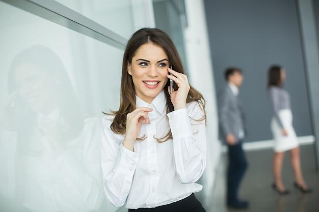 Mujer joven en la oficina con teléfono móvil