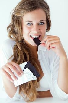Mujer joven en ropa interior comiendo chocolate. aislado en blanco