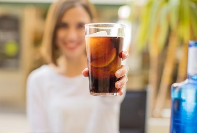 Mujer joven en un restaurante con una coca cola