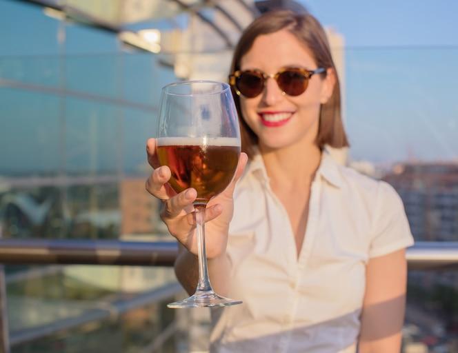 Mujer joven en una azotea con una cerveza