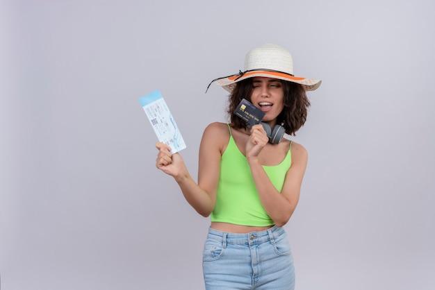 Una mujer joven encantadora confiada con el pelo corto en la parte superior verde que lleva el sombrero para el sol que muestra los billetes de avión y la tarjeta de crédito sobre un fondo blanco