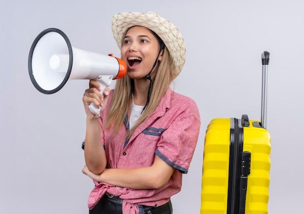 Una mujer joven encantadora feliz con camisa roja y sombrero para el sol hablando por megáfono en una pared blanca